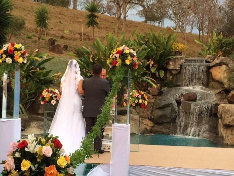 Na foto um casal de noivos realiza seu casamento em frente á cascata . Realize seu evento em um hotel fazenda perto de bh